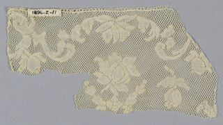 Valenciennes fragment with lower edge missing. Design very fragmentary with a rose in the center. Top border design has swinging scrolls and buds. Round mesh.