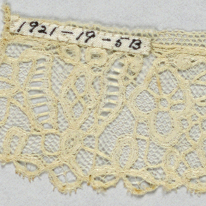 Cuffs made of bobbin lace applied to machine-made net in a pattern of flowers and leaves.