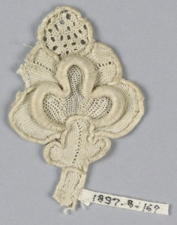 Fragment of raised lace with a highly conventionalized design of a pomegranate bud with an openwork tip.