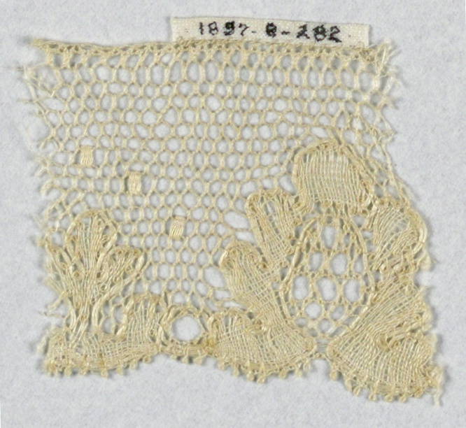 Border fragment of Lille-style lace in a highly conventionalized floral design. Small square dots above.