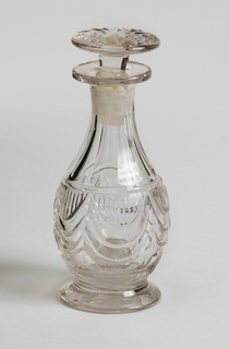 One of set of seven bottles. Bottle has bulbous body with tapered, narrow neck ending in flat, circular pouring lip. Flat circular foot. Body encirlced with band of cut drapery swags filled in with vertical lines. Flat flutes on neck and below band. Stopper is stemmed button variety, flat with radial cutting.
