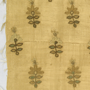 Small symmetrical Mughal-type embroidery of sprigs in light green diagonal repeat across the grain of satin ground. Piece has apparently been dyed for ground is deep shade of golden tan now in shades of tan and brown, faint green. Two narrow twilled selvage edges are hand-seamed across middle.