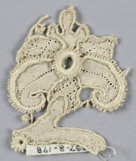Fragment in a design of a flower with five petals, stem and a portion of the leaf or stem. Three of the petals in a diamond diaper pattern. Two largest petals have picot edge.