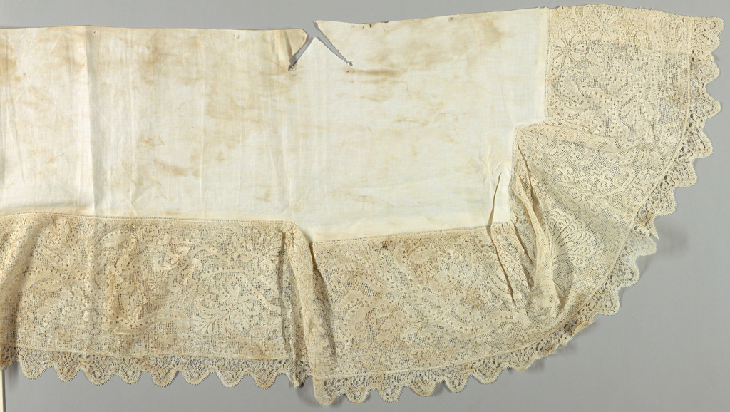 A shaped linen cover in plain white which has a wide border of filet lace in an elaborate, fantastic design of curving vines and flowers with a winged, four-footed beast. Edged with scalloped bobbin lace. The border is backed with course, modern net to protect it.