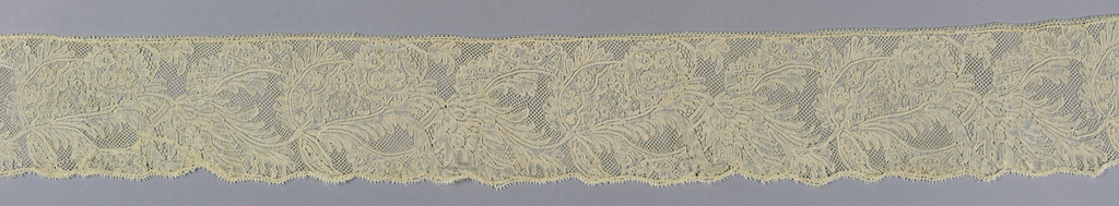 Mechlin lace worked with a design of a plumed leaf form and conventionalized floral motifs with five hole ground and snow ball fillings.