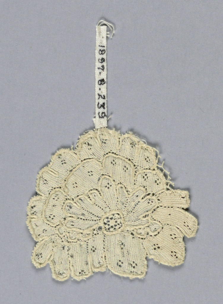 Fragment of Argentan lace with a complete flower and a small bit of ground attached at one side.