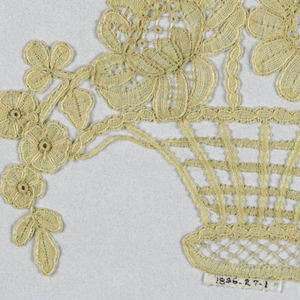 Large basket with tall handle has a ribbon bow and is filled with flowers.