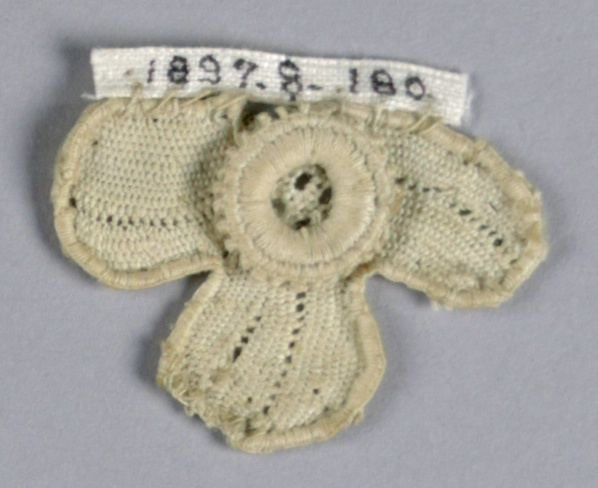 Fragment in a pattern of a small trefoil blossom with a central superimposed rosette.