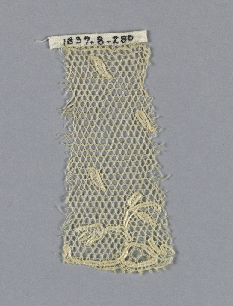 Fragment of Lille-type lace with a border design of small floral sprays. Small oval leaves scattered over the ground.