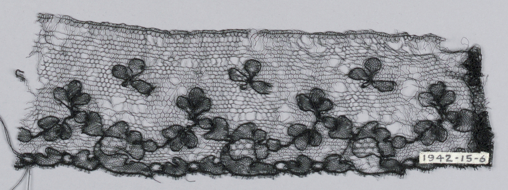 Fragment showing a design of flowers made with outlining thread and honeycomb fillings sprinkled on a ground of hexagons and arranged as a border.