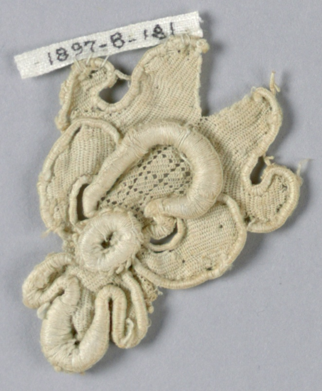 Fragment in a pattern with a blossom with deeply scalloped petals. Central superimposed rosette. Diamond diaper pattern on one petal.