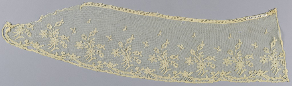 White imitation Carrickmacross; pattern of floral sprays cut in muslin and applied to machine net; one ornamental edge.