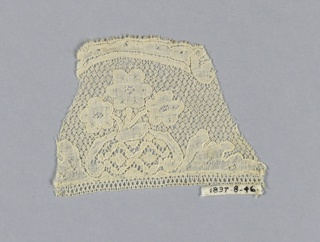 """Fragment of Mechlin lace with conventionalized floral spray with broad leaves. Variety of """"fond de neige"""" ground."""