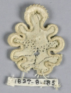 Fragment with a leaf in an openwork design and deeply scalloped edge.