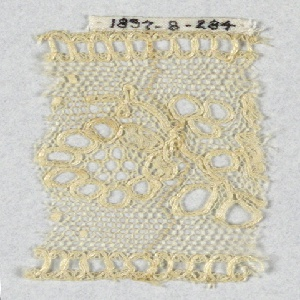Fragment of Lille-style lace with oval conventionalized blossom and leaves in eyelets. Beading top and bottom edge.