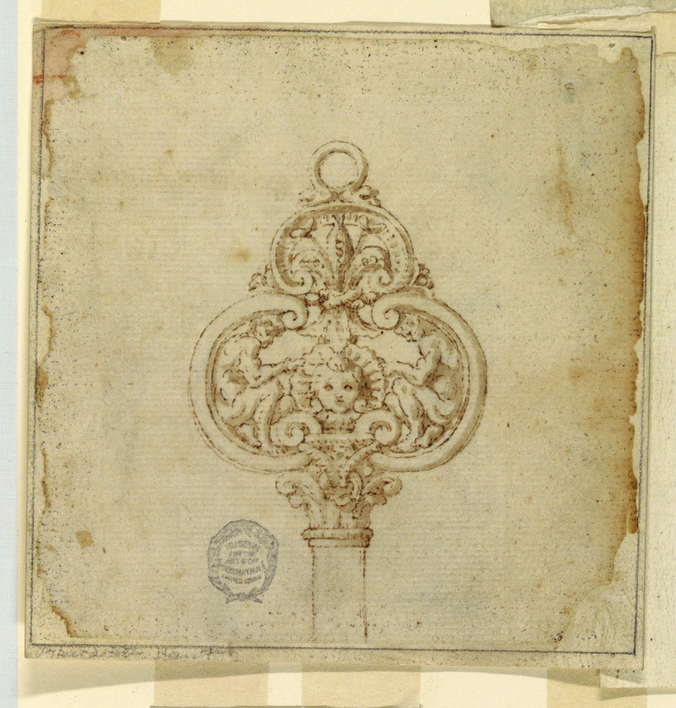 Trefoil ornament with fleur-de-lys. Within, two figures and a mask. Ring at top.