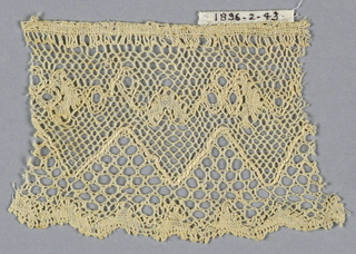 Lille-style fragment with upper portion in a conventionalized pattern separated from border by deep points with heavier thread.