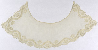 Round net collar with an scalloped border edged with triangular tabs. Leafy vine runs along three sides with oval groups of flowerheads in the interstices.