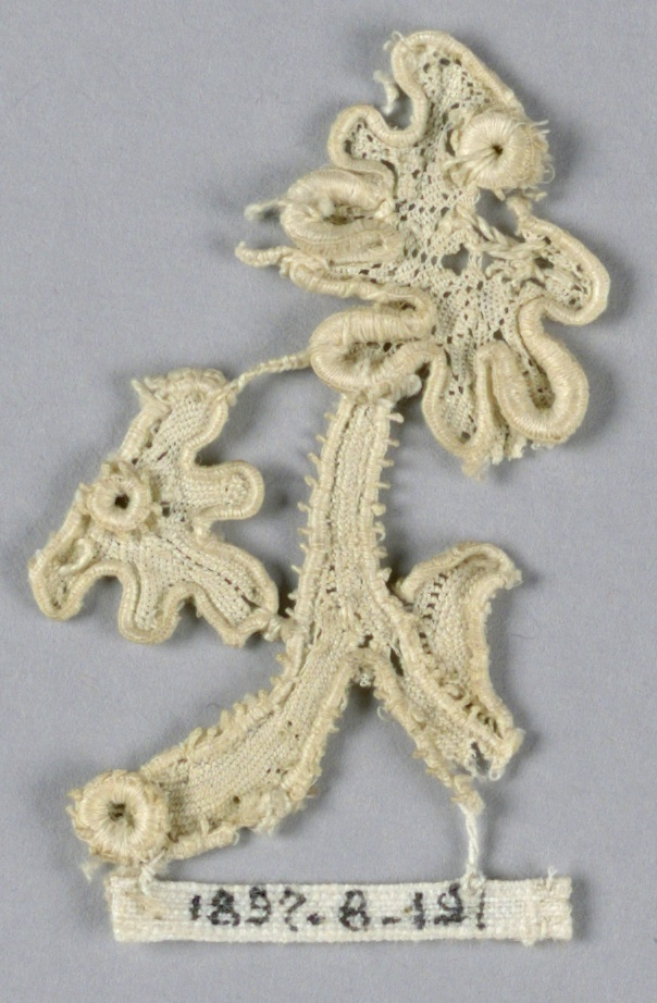 Fragment in a pattern of a small branch with a portion of two small scalloped blossoms attached to it.