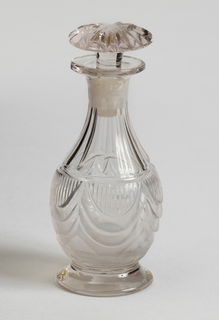 Pear-shaped body cut with drapery swags and flat vertical fluting; flat circular foot; mushroom-shaped stopper with radial cutting. One of set of seven bottles, but a modern replacement. Identical to ?