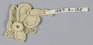 Fragment in a pattern of a flower with a scalloped edge. Partly in openwork. Several tiny superimposed rosettes.