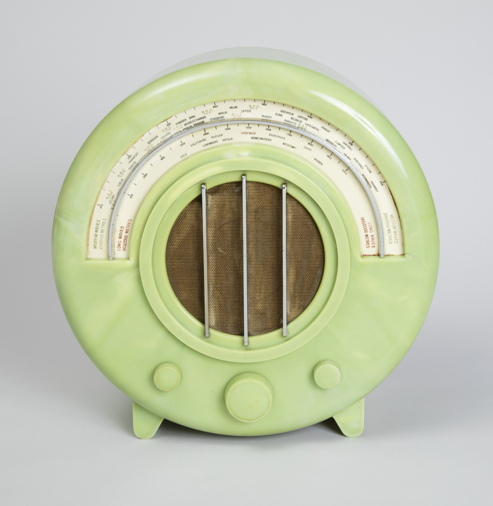 Circular green Bakelite housing with semi-circular station dial at top front above circular brown textile-covered speaker with three vertical metal rods as grille; three circular control knobs below speaker; two angled feet at base.