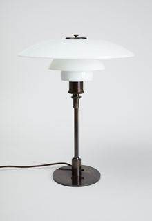 Three-tiered curved shade composed of three separate glass segments of graduated sizes stacked on an internal metal support, all on a simple dark brown patinated metal base consisting of a vertical rod on a circular foot; circular, metal screw-on cap with circular finial at top of shade.