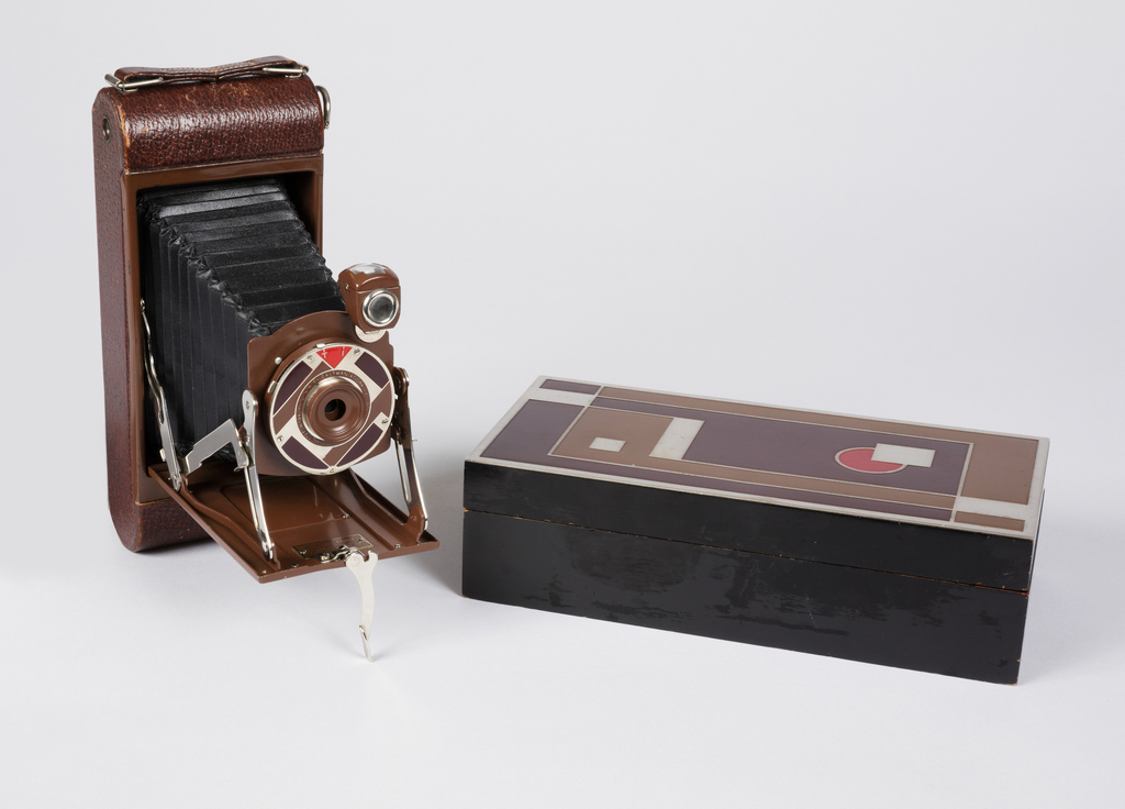 Rectangular folding camera (a) with rounded edges, the front panel decorated with geometric design of black and silver squares, rectangles, and a red circle. Front panel hinged to open and reveal bellows with lens in circular ring also enameled in red, brown and tan. Rectangular black-lacquerd cedar case (b,c) with same geometric design as on camera repeated on lid.