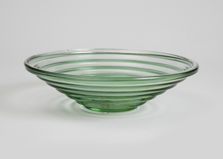 Wide mouthed, shallow, circular stepped form of green-tinted transparent glass.