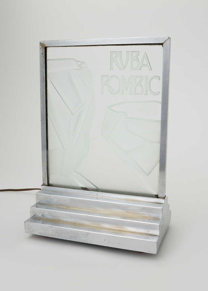 "Glass plate with engraving of 2 angular rock-like shaped vases with ""Ruba Rombic"" written in capital letters, encased in a chrome-plated metal frame with a 3-tiered base"
