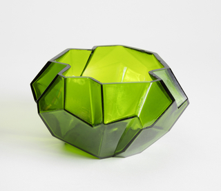 Wide low angular dark green vase, asymmetrical form mimicking a rock, with a wide opening