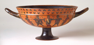 Wide shallow bowl on flaring foot, two loop handles oriented horizontally.  Exterior decorated with two groups of young men armed with spears, facing central figure of Dionysus who holds drinking horn.  Above, a double ivy wreath border; below, meander and rays.  Interior centered with confronting cloaked figures holding spears.  Red and black on red ground.