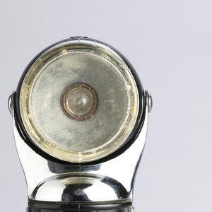 Black spherical swiveling head with flat circular clear lens attached to white metal housing on ridged tubular black plastic body; white metal on/off switch on side. Circular base (b) with metal ring unscrews from body for access to battery compartment.