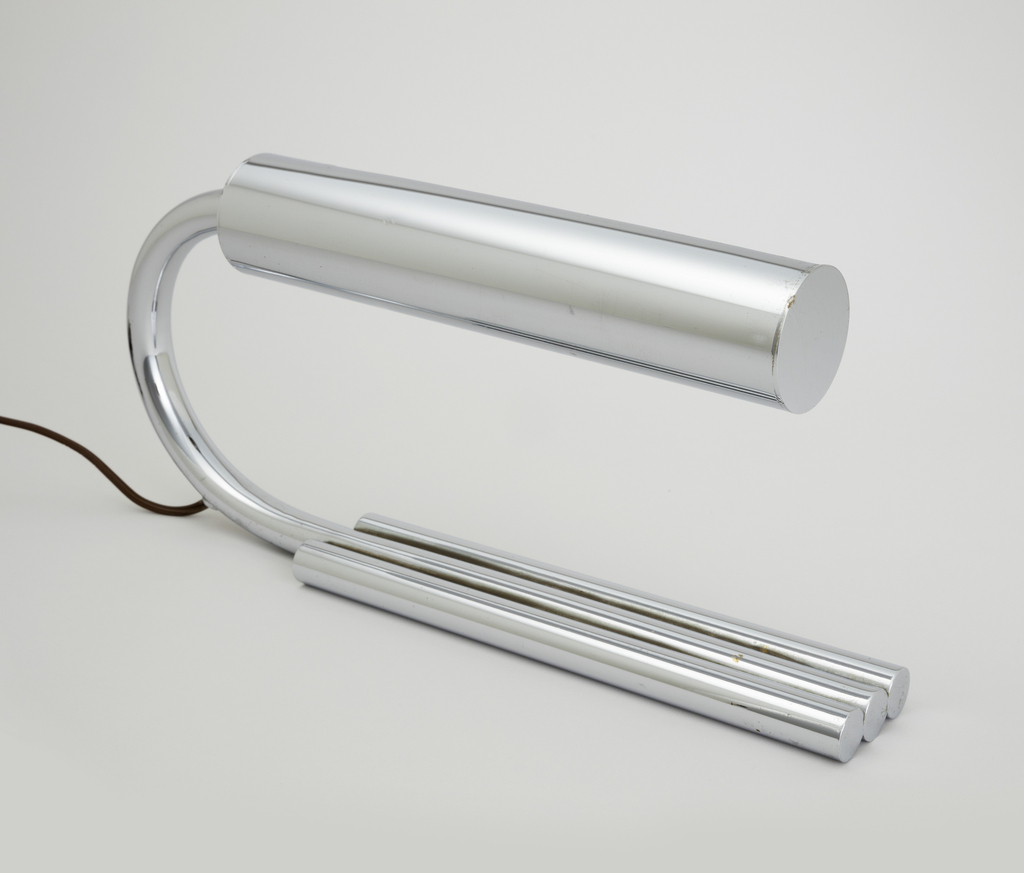 Base composed of three horizontal chrome-plated rods, the center rod up-curved to form a C-shaped support for a horinzontal cylindrical shade fitted with a tubular incandescent light bulb.