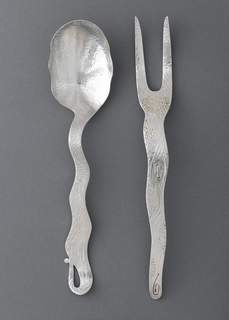 A serving spoon with a wood grain textured finish and slightly undulating handle.