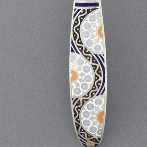 Gilt silver spoon with black, blue, white, and orange geometric and circular patterns in enamel on handle.