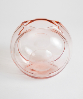 Globular shape of pink transparent glass molded with concentric circles; large mouth at top.