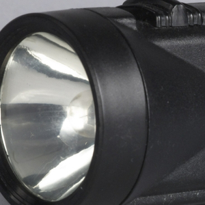 One-piece black plastic body of flat rectangular form flaring into circular lamp housing; black plastic on/off switch at top near lamp.