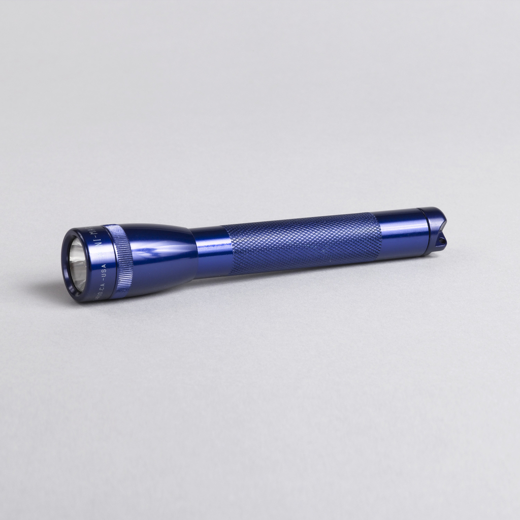 Blue-purple toned long cylindrical shaft, with knurled grip section, topped by narrow tulip-shaped head with clear lens. Removeable circular cap at end unscrews to reveal battery housing; spare bulb stored in cap.