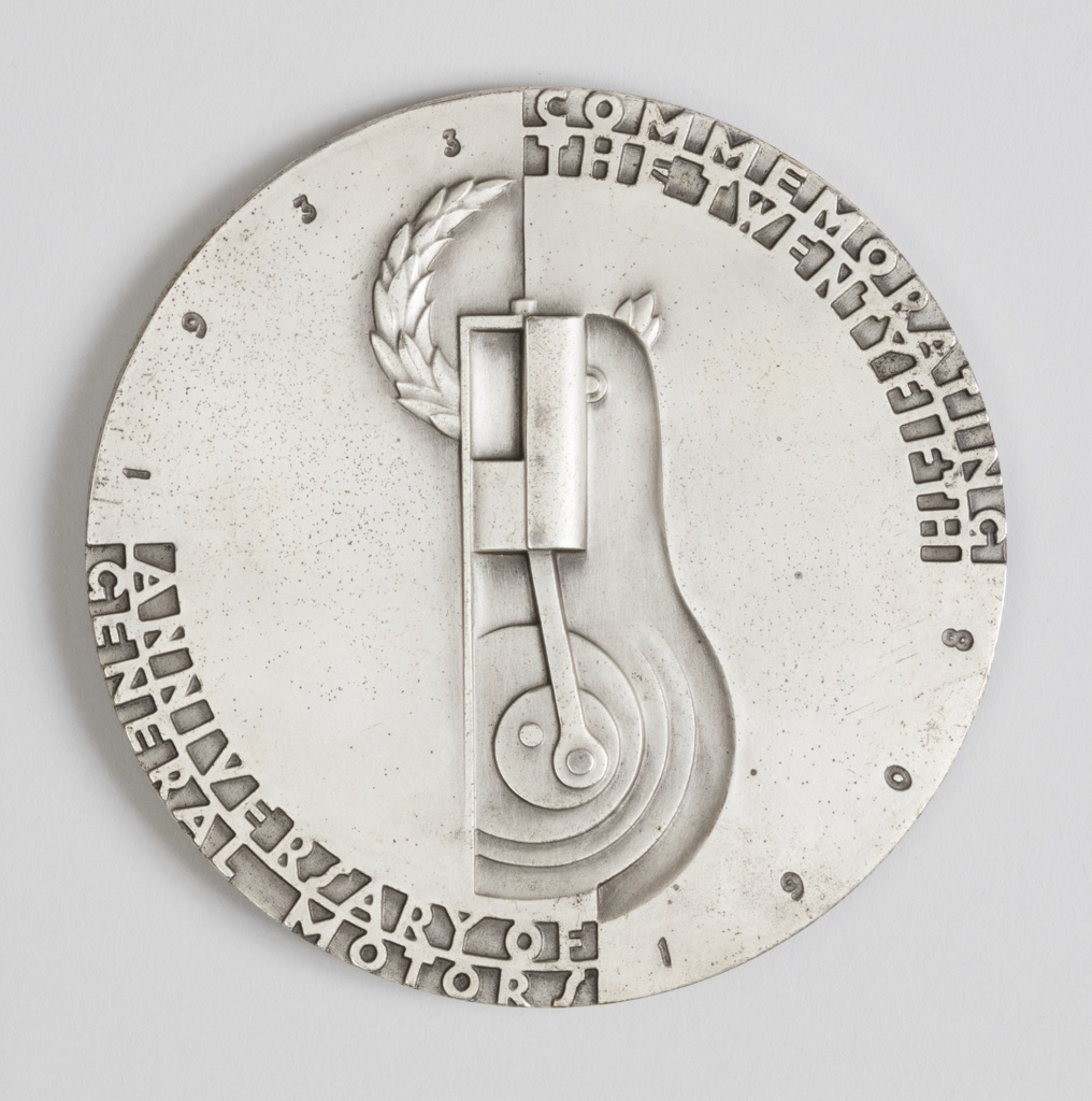 Circular form. Obverse depicts an eight-wheeled Art Deco Streamlined-style auto (Bel Geddes' Motor Car No. 9) as it speeds to the right; a large upright wing towering over it (Motor Car No.9 featured a vertical stabilizer, or rudder, in its tail, like an airplane.) The smooth field is broken by two recessed rim segments at top right and lower left bearing the raised-letter legend: to the advancement of – motor transportation. Signed below car: NORMAN BEL GEDDES ©1933.  Reverse is divided vertically by a stylized automotive engine piston design, and laurel wreath above. Small incuse dates 1908 – 1933 around the rim diagonally from bottom right to top left; recessed rim segments bearing the two concentric-line legend: commemorating/ the twentyfifth – anniversary of/ general motors.