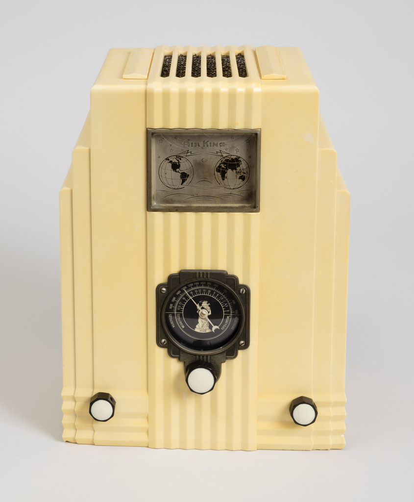 Rectangular, box-like form of light yellow plastic with stepped sides. The front molded with a series of seven vertical striations from top to bottom, and four horizontal ones near base; three white control dials and a large black dial at the center with number scale and image of Atlas holding up the globe; metal plaque at front top showing map of the world; rectangular speaker grill over woven textile on top.