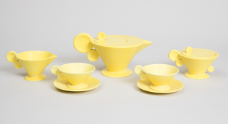 The yellow, glazed coffee pot is in the shape of an inverted cone. The opening for the circular lid is off-center, as is the finial (in the shape of a disc standing on its edge) on the lid. The spout is in the shape of a pyramid, while the handle is made of two discs touching one another.