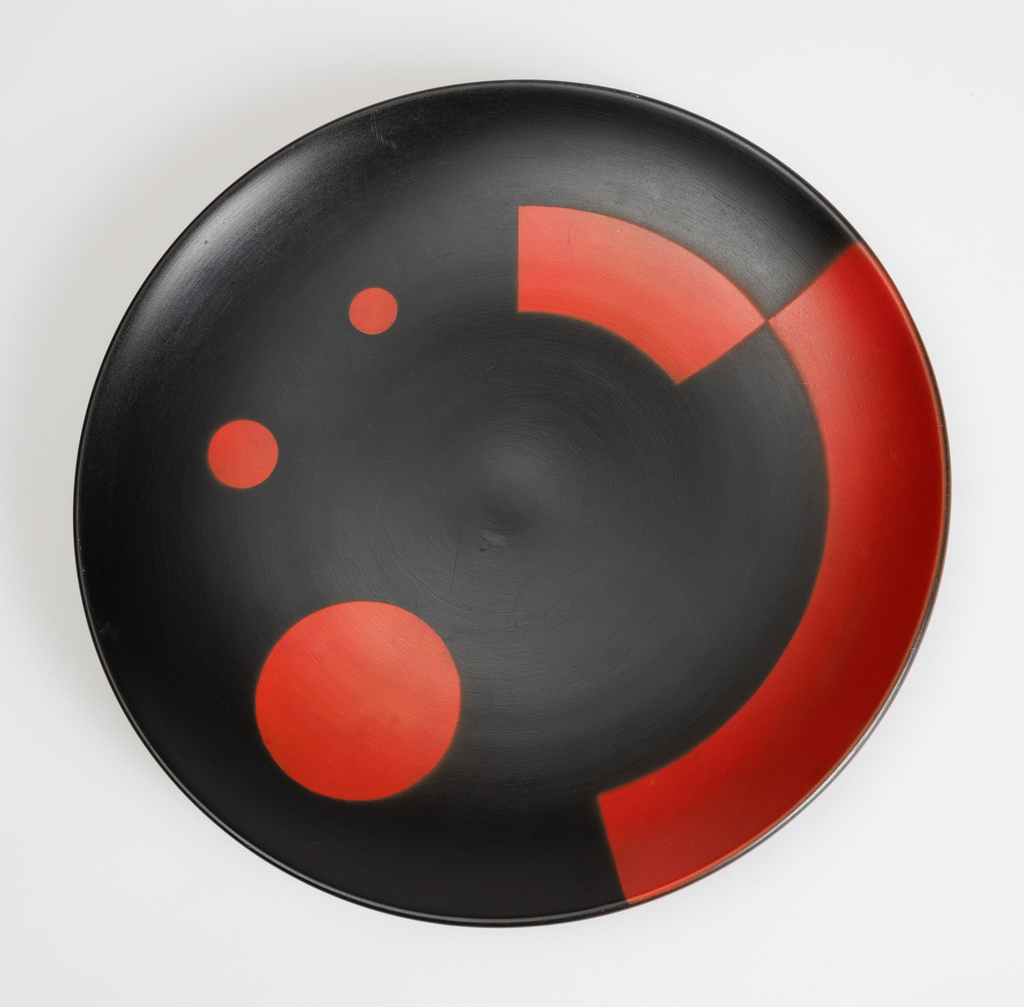 Circular form, with red circles and curved panels on a black background.
