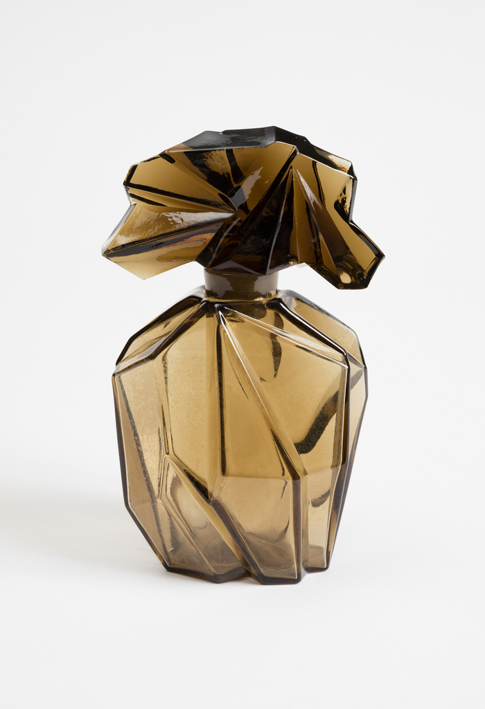 Transparent brown glass bottle (a) with narrow, short neck and a flared mouth; body molded to form irregular geometric shapes and angles, resembling crinkled paper. Stopper (b) similarly molded and resembling fanned crinkled paper form.