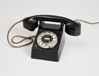 Black-enameled brass rotary telephone with nickel-plated brass rotary dial and black Bakelite receiver; white faceplate with black numbers under dial; black ring with white letters, A,B,C,D,E,F,G,H,J,K, and manufacturer's logo, TM, within dial.