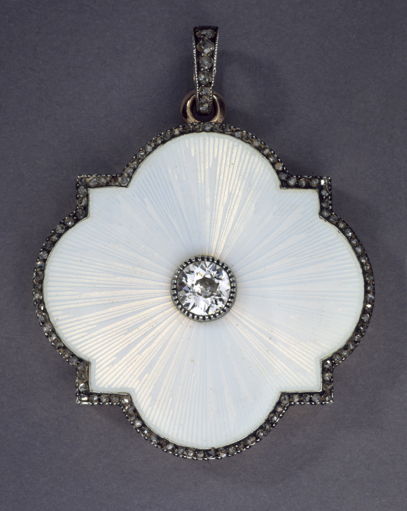Quatrefoil shape with square projections, the top engine-turned under white enamel centered by a .50 kt round old mine cut diamond and surrounded by approximately .75 kts of rose-cut diamonds; opening to reveal two circular locket compartments in yellow gold; with gold and diamond bail. Together with a white gold chain.