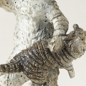 Gray, black, and white tabby cat standing on hind legs holds an upraised stick above a mewing kitten lying across its knee, as if in the act of spanking.
