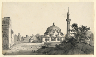 Horizontal rectangle. Mosque on square surrounded by other buildings. Rocks, shrubbery, and monument in foreground.