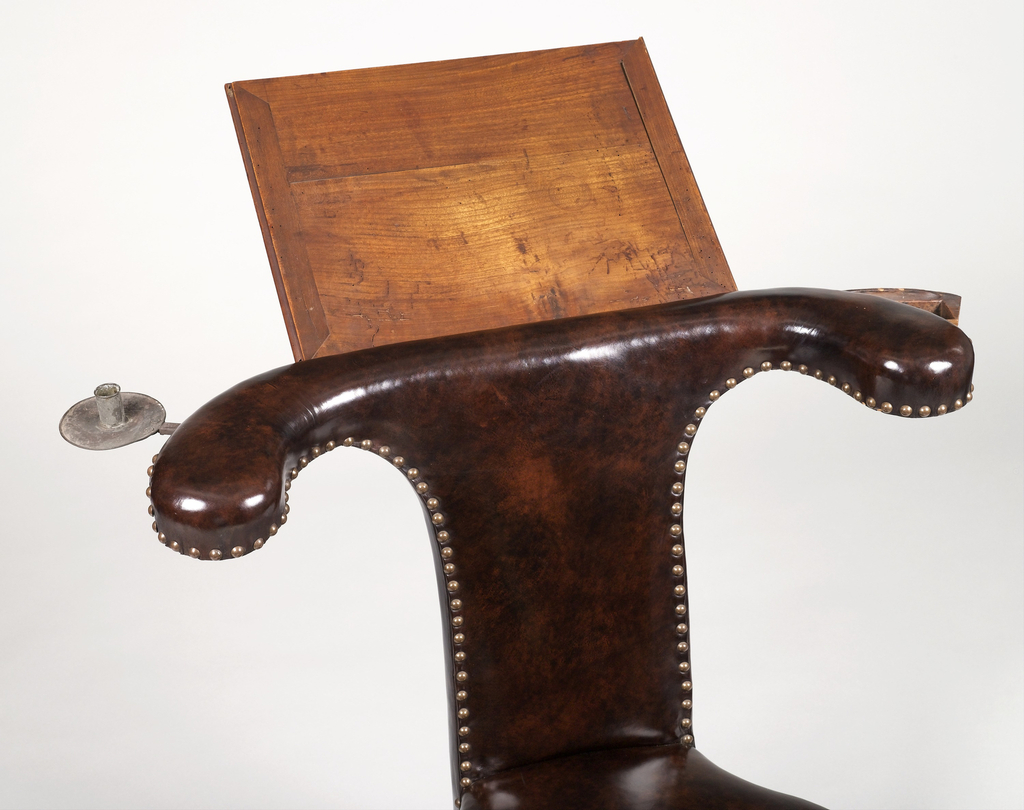 Form with square tapering seat and tall narrow back upholstered in dark brown nailed leather; back with horizontal U-curved arms at top fitted with hinged, adjustable wooden book rest on back; retractable tin candleholder in left arm, small retractable sectioned tray in right arm; drawer in seat; cabriole front legs with pad feet, turned stretchers, rear feet square in section; small brass caster on each foot.  A) chair B) drawer C) bookrest support