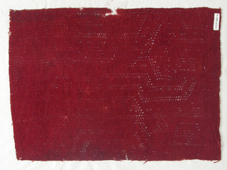 Fragment of a red cotton shawl or mantle in which a geometrical design is executed in an open work or lace effect.